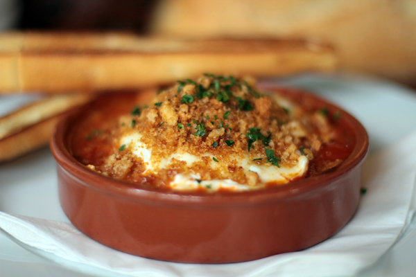 Baked eggs puttanesca with Schiacciata