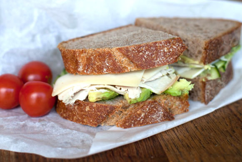 Picture of sandwich with three tomatoes next to it